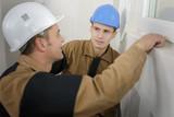 Two workmen by pvc window - 185502410