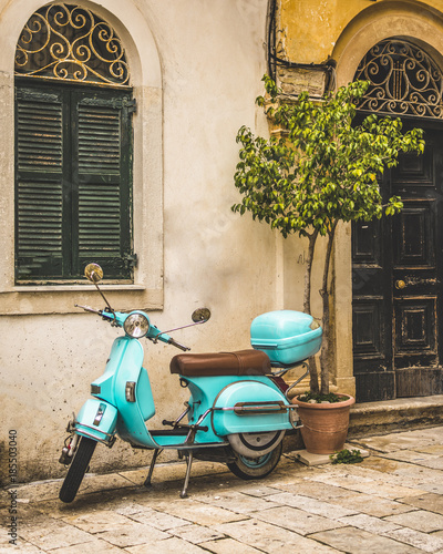 Plexiglas Scooter Corfu, Greece- December 21, 2017: Narrow streets and alleys in Corfu town Greece.Architecture in the old town of Corfu is heavily influenced my the Venetian architecture.Blue Vespa outside a building.