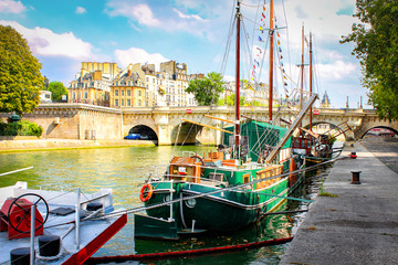 Yachts and boats on river Seine in Paris on summer sunny day. France Paris city landscape on bright day. Streets of the French capital.