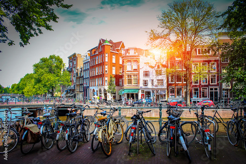 Amsterdam. Parking for bicycles on background of old city at sunset in capital of Netherlands. Streets for walks in Amsterdam.