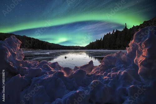 Fotobehang Nachtblauw snowdrift in the foreground under an aurora borealis