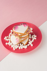 close up view of heart shaped cookies and marshmallow on pink plate