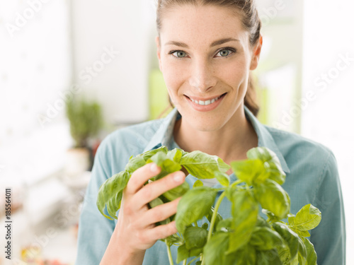 Woman holding a plant of fresh basil