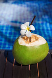 Fresh coconut juice with straw and plumeria, frangipani flower on border of a swimming pool