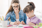 Young mother and girl drawing together