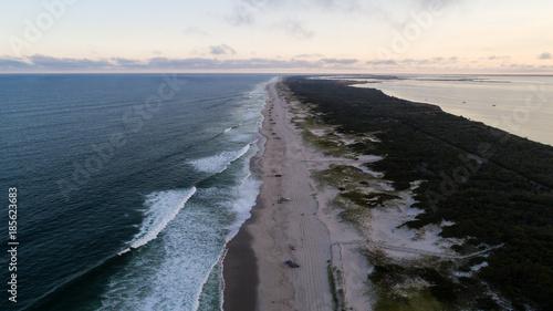 Foto op Canvas Zee zonsondergang trucks lined up on a beach in summer