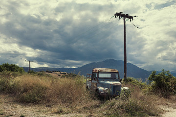 Old retro car on the mountain landscape background. Old car in a thunderstorm