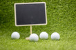 Golf school training concept with chalkboard and golf balls on green grass