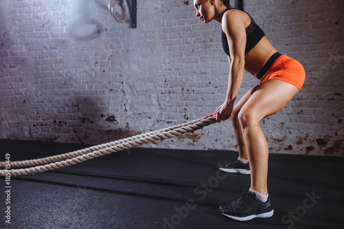 Woman training with battle rope in cross fit gym