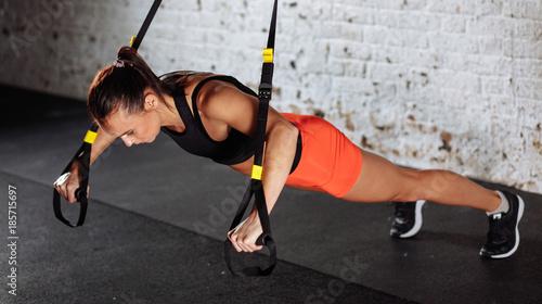 Kobiety robienie pompek treningu broni z trx fitness pasy w siłowni