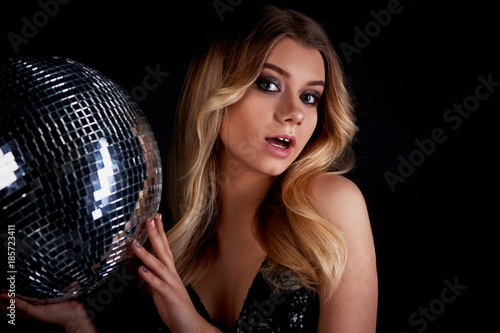 The blonde laying in the style of Abba holds a disco ball. The era of disco. Night club, dancing - 185723411