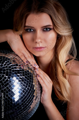 The blonde laying in the style of Abba holds a disco ball. The era of disco. Night club, dancing - 185723479