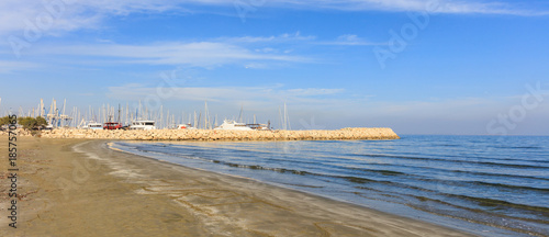 Staande foto Cyprus Sandy beach with distant view of Larnaca marina at Cyprus. Blue sky and white clouds background.
