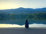 lonely man sitting by the lake - 185773639