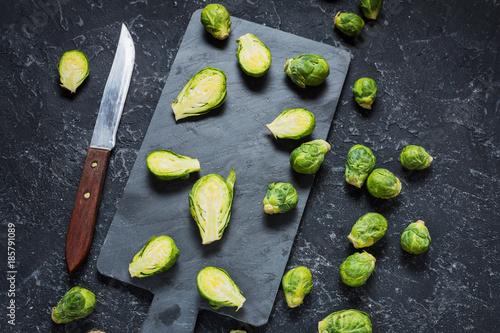 Papiers peints Bruxelles Brussels sprouts and knife on stone chopping board and black background