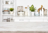 Fototapety Wooden table over blurred image of kitchen bench and shelf