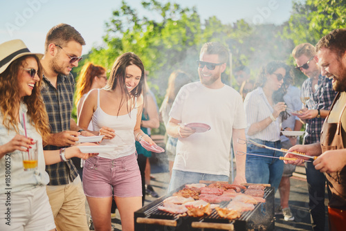 Foto Murales Group of people standing around grill, chatting, drinking and eating.