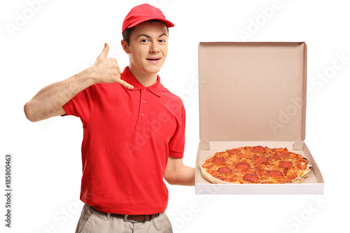 Teenage pizza delivery boy holding a pizza box and making a call me gesture - 185800463