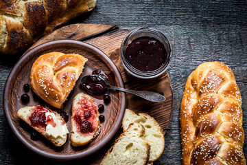 Challah is a Jewish bread to the feast on the dark wooden boards.