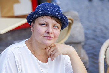 MOSCOW, RUSSIA, on August 10, 2017. The attractive woman in a blue hat poses for the photographer and smiles