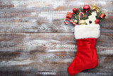 Fototapety Red stocking and christmas decorations on wooden table