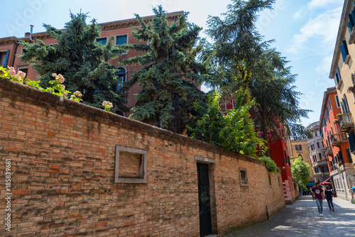 Beautiful venetian street with old houses in a sunny summer day.