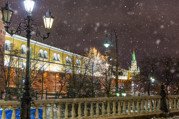 Moscow Kremlin wall and street lamps during snowstorm at night in Russia