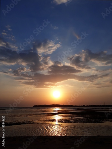 Aluminium Strand Warm dramatic sunset at a beach during low tide portrait