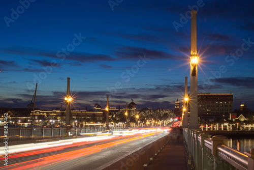 Fotobehang Nacht snelweg City and bridge decorated with lights at twilight against blue sky showing traffic passing through shot from the bridge looking at the city