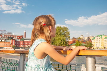 little girl with pigtails stands on embankment and looks at city