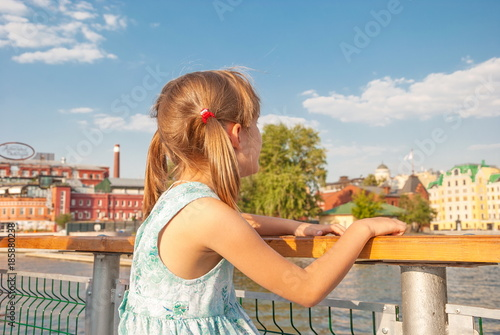 Foto op Aluminium Moskou little girl with pigtails stands on embankment and looks at city