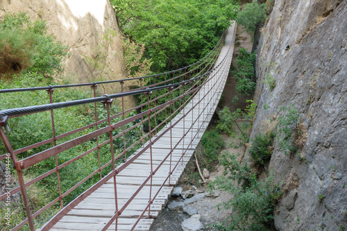 Iron and wooden suspension bridge in canyon