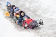 children having fun riding ice slide in snow winter