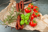 pork sausages and cherry tomatoes on a stone table - 185901218