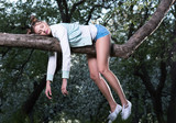 Wild fatigue. Beautiful young woman sleeping on a tree branch. Feet and hands hanging down - 185915450