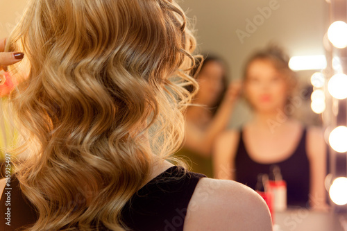 Close up of curly hair and blurred reflection of hairdresser making curls in beauty salon.