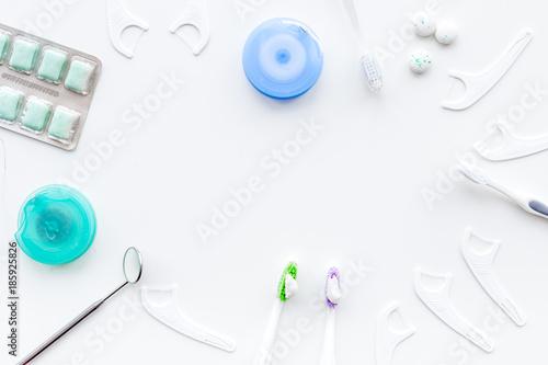 Foto Murales Teeth care. Toothbrushes, floss, gum dental mirror on white background top view copyspace