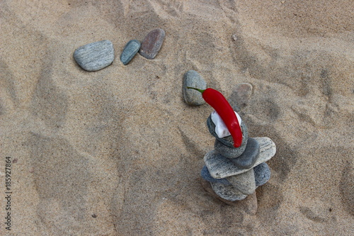Foto op Canvas Stenen in het Zand The background of a sandy beach with balanced zen stones and hot red pepper