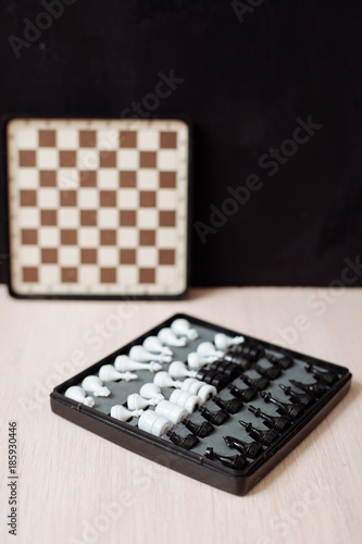 Chess and checkers on a wooden table and black background. - 185930446