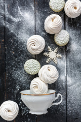 Homemade marshmallows and macarons with winter decor.