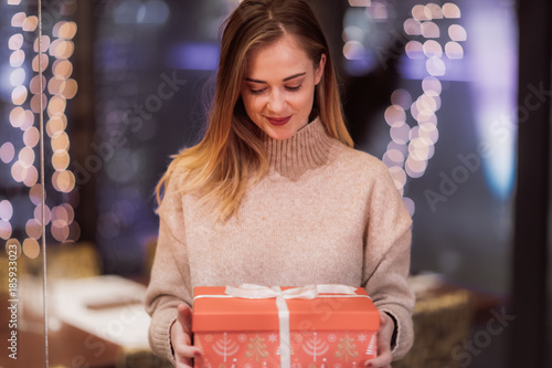 Two cute young adolescent women, heavy loaded with christmas gifts,  shopping, while walking along store windows and choosing and admiring the items.
