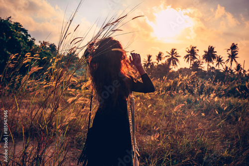 Foto Murales sunset portrait of beautiful young woman on a field