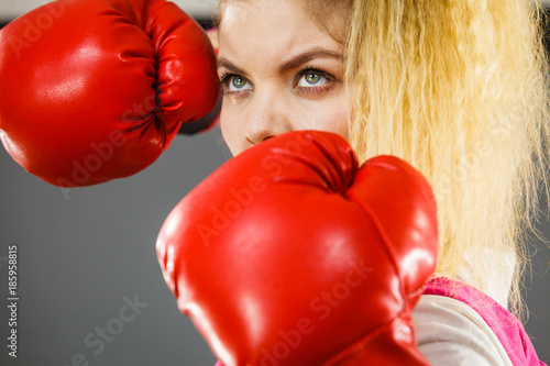 Angry woman wearing boxing gloves Photo by Voyagerix