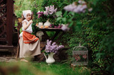 kid girl at garden tea party in spring day with bouquet of lilacs (syringa), rustic wooden table and vintage dress - 185964285