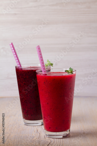 Foto op Plexiglas Milkshake Frozen summer berries smoothie: blueberries, strawberries, raspberries, cranberries, currants and blackberries on wooden background, vertical