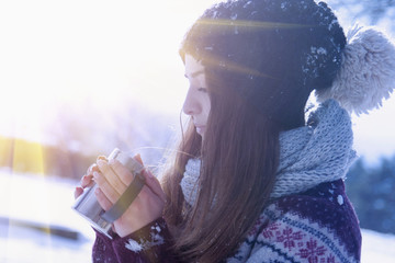 Close up of young beautiful woman drinking hot beverage. (Christmas, new year, celebration concept)