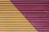 Corrugated metal door painted in two colors: red and yellow - 186033606