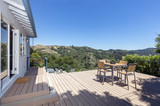 Open patio door with new outdoor patio / wooden deck with outdoor furniture and mountain view. - 186068036
