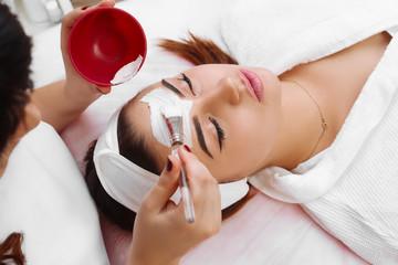 Beautiful woman with facial mask at beauty salon