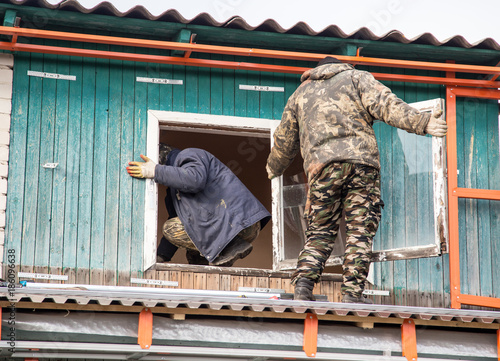 Foto Murales Workers remove the old window in the house